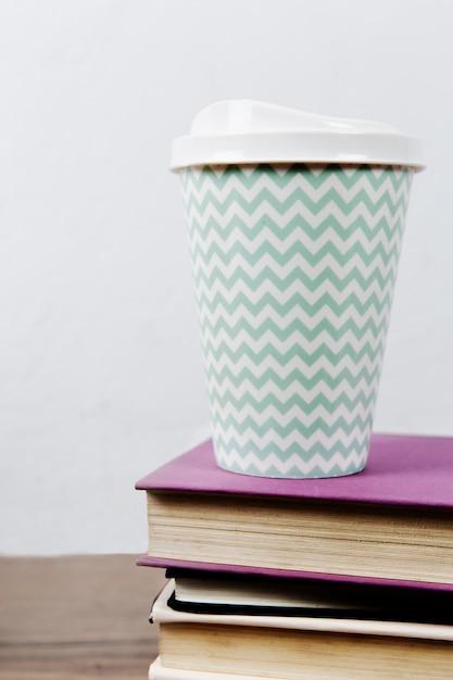 Taza de café en la pila de libros. Foto gratis