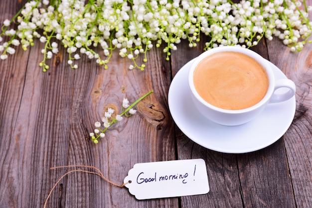 Taza de café en un platillo, junto a un ramo de lirios blancos del valle Foto Premium