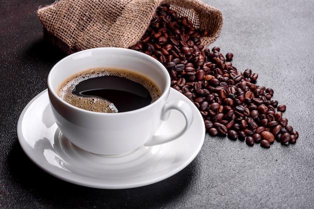 Una taza de café recién perfumado para un comienzo alegre del día. hermosa taza de café con café en una mesa oscura Foto Premium