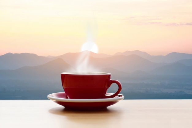 Taza de café roja con sol de mañana vista a la montaña Foto Premium