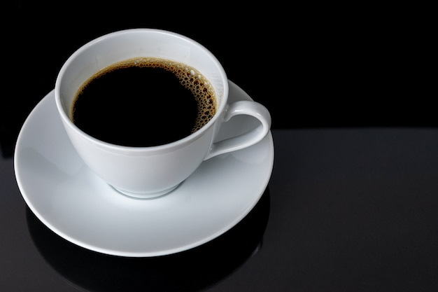 Taza de café sobre fondo negro. Foto Premium