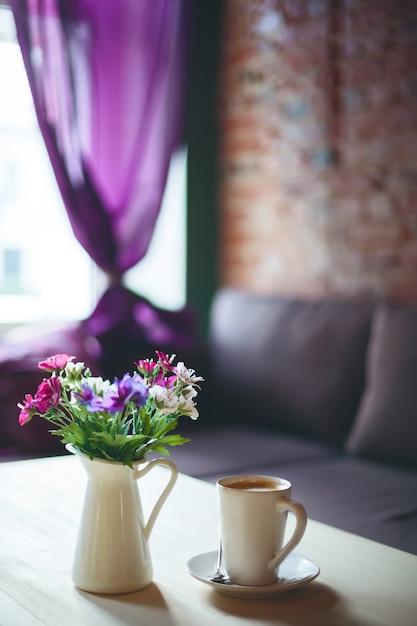Taza de café sobre la mesa en la cafetería vacía Foto Premium