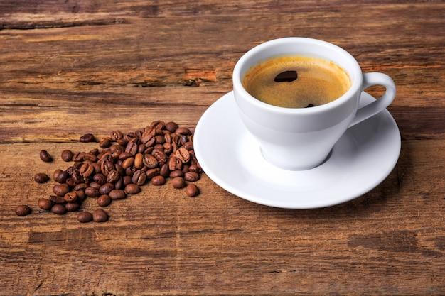 Taza de café sobre una mesa de madera. fondo oscuro Foto gratis