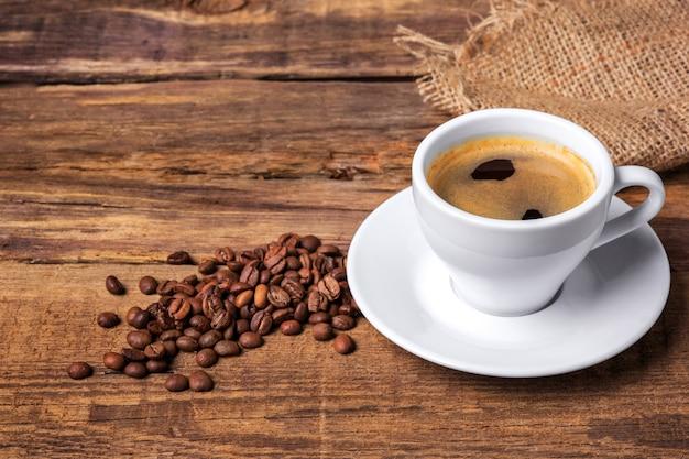 Taza de café sobre una mesa de madera. muro oscuro Foto gratis