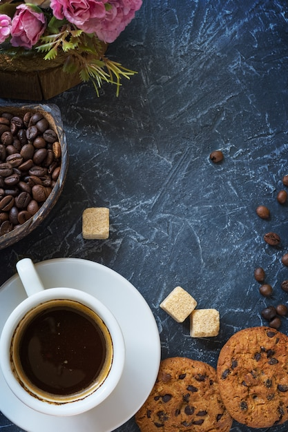 Una taza de café con trozos de azúcar de caña, galletas con chocolate y un jarrón con granos de café. Foto Premium