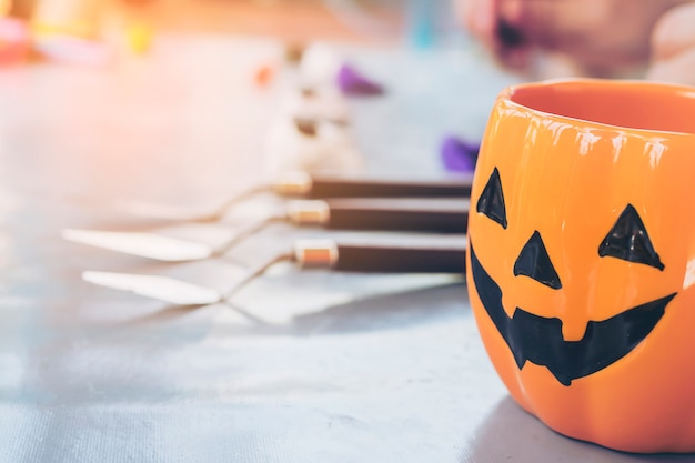 Taza de la cara de la linterna del enchufe o de halloween sobre el muchacho borroso que esculpe el fondo del juguete de la arcilla Foto gratis
