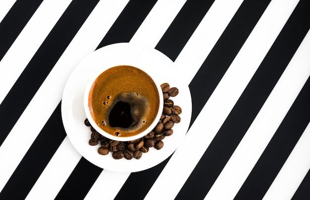Taza de cerámica blanca de café fuerte sobre fondo de rayas Foto Premium