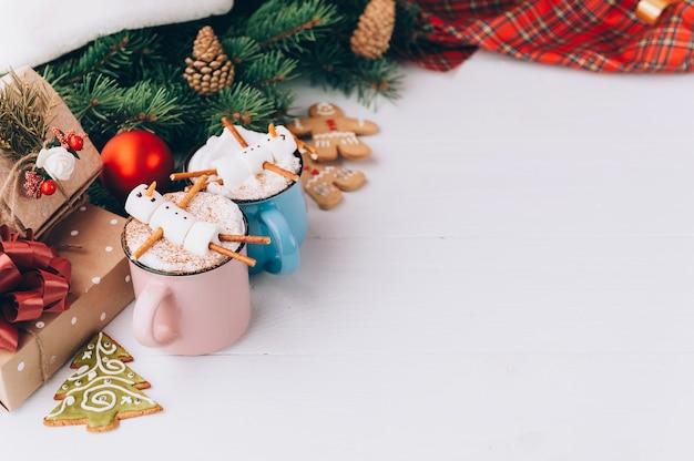 Una taza con chocolate caliente en una mesa de madera con un hombre de malvavisco que está descansando en una taza Foto Premium