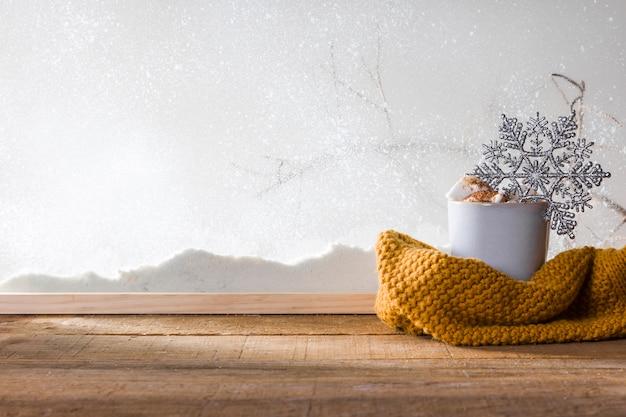 Taza con copo de nieve de juguete cerca de bufanda en mesa de madera cerca de banco de nieve Foto gratis