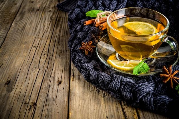 Taza de cristal de té con limón, menta y especias, en la vieja mesa de madera rústica con mantas calientes. Foto Premium