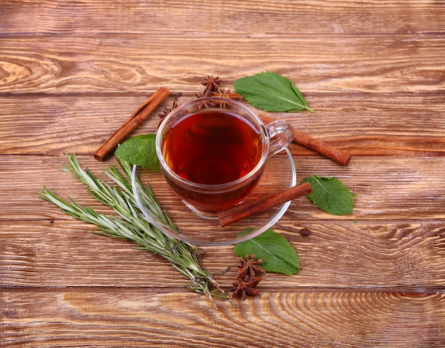Taza de cristal de té verde con canela sobre un fondo de mesa de madera. Foto Premium