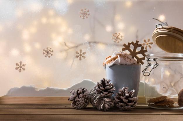 Taza con ganchos y lata en una mesa de madera cerca del banco de nieve, planta ramita, copos de nieve y luces Foto gratis