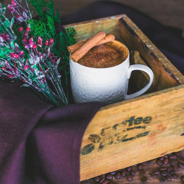 Taza de latte adornada con palitos de canela servida en caja de madera con rama de árbol Foto gratis