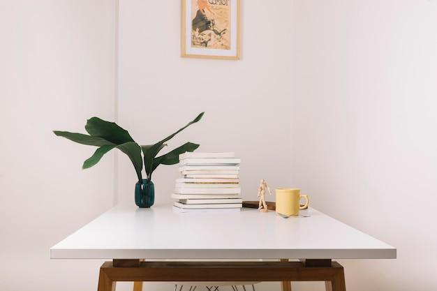 Taza y libros sobre la mesa cerca de decoraciones Foto gratis