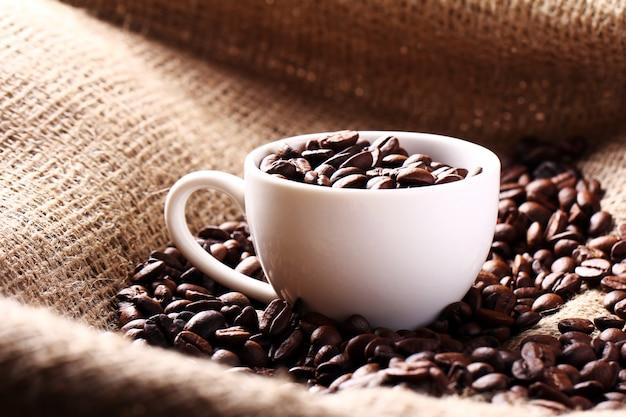 Taza llena de granos de café Foto gratis
