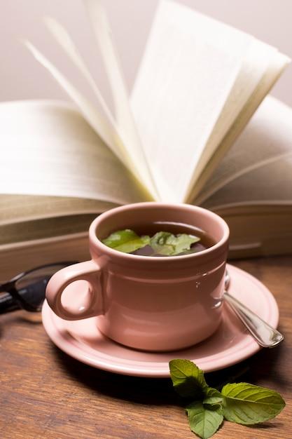 Taza marrón de té de hierbas con libro sobre la mesa Foto gratis