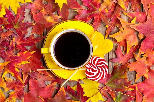 Taza con paletas de café negro, rojo, amarillo en la mesa de madera con hojas amarillas, naranjas y rojas caídas en otoño Foto Premium