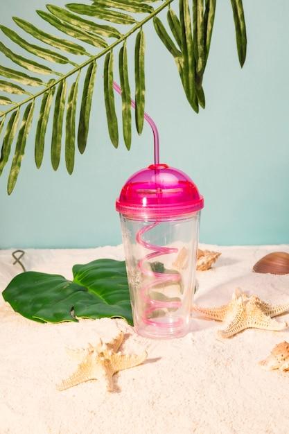 Taza plástica con paja en playa Foto gratis