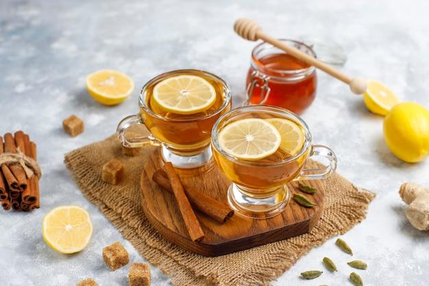 Una taza de té, azúcar morena, miel y limón sobre hormigón. vista ...