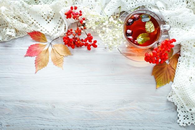 Una taza de té y de bayas de serbal en una tabla de madera. bodegón de otoño. Foto Premium