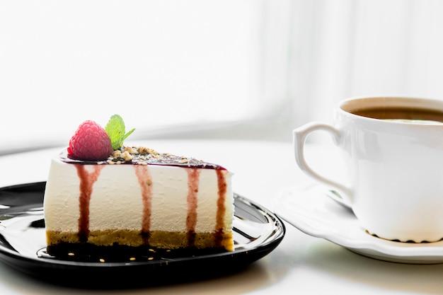 Taza de té cerca del pastel de queso casero con bayas frescas y menta para el postre en la mesa Foto gratis