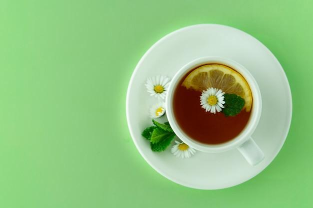 Taza de té y chamomiles. concepto de té natural a base de hierbas. taza blanca de té con flores de manzanilla. Foto Premium