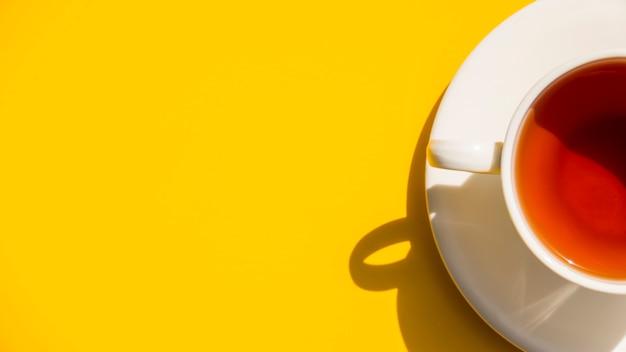 Taza de té flat lay sobre fondo amarillo Foto gratis