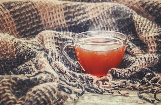 Una taza de té y un fondo acogedor de otoño. enfoque selectivo Foto Premium