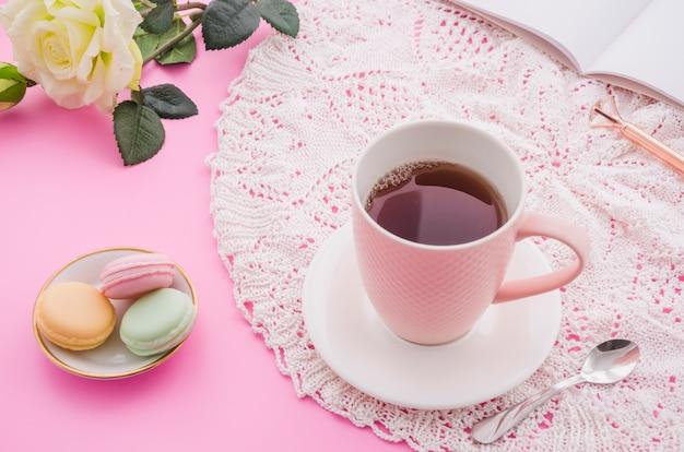 Taza de té de hierbas con macarrones; cuchara; rosa; pluma y libro sobre fondo rosa Foto gratis