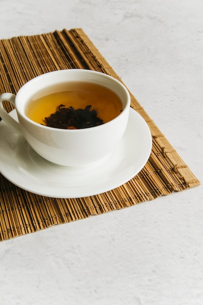 Taza de té de hierbas en mantel individual sobre el fondo de hormigón Foto gratis