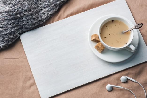 Taza de té con leche, azúcar de anís marrón y un bloc de notas. Foto Premium