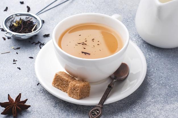 Taza de té con leche, azúcar de anís marrón sobre una mesa gris. Foto Premium
