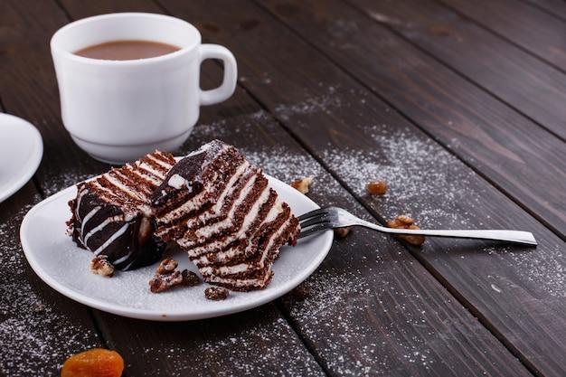 Taza de té con leche y dos platos con tarta de queso y chocolate Foto gratis