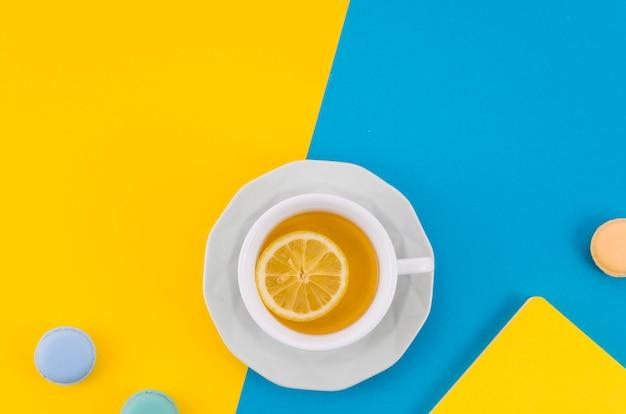 Taza de té de limón con macarrones sobre fondo doble amarillo y azul Foto gratis