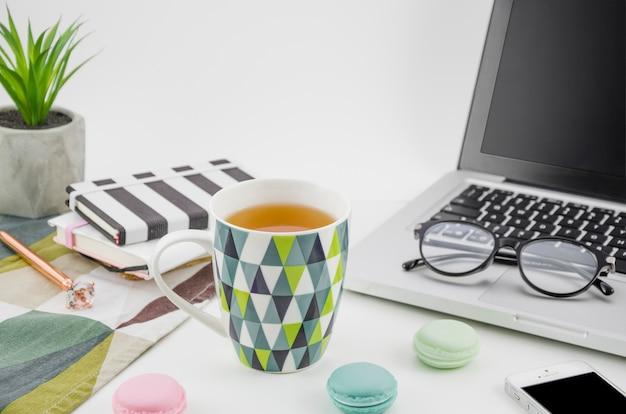 Taza de té con macarrones en la mesa de trabajo blanca con computadora portátil y teléfono móvil Foto gratis