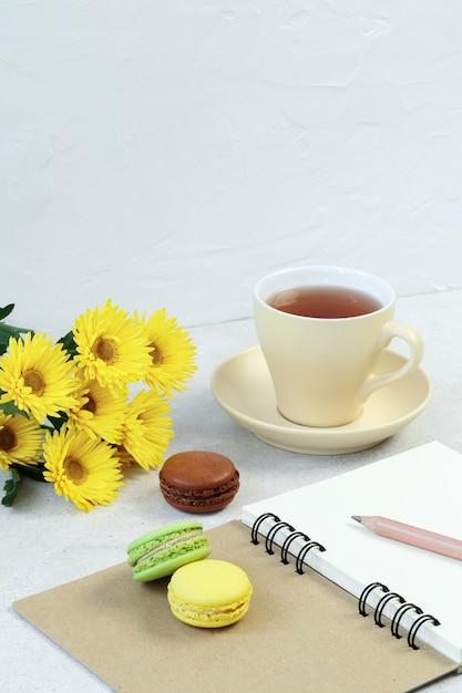 Taza de té, macarrones y notas sobre mesa de hormigón. Foto Premium
