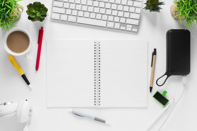 Taza de te macetas; bloc de notas espiral taza de té y bolígrafos en el escritorio blanco Foto gratis