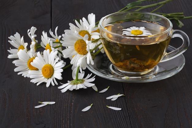 La taza de té de manzanilla herbario con la margarita fresca florece en fondo de madera. tratamiento médico y prevención del concepto inmune Foto Premium
