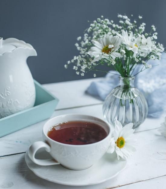 Una taza de té y margaritas blancas sobre una mesa blanca. Foto gratis