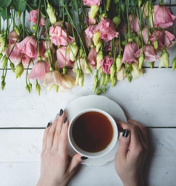 Una taza de té negro y flores amarillas y rosadas Foto gratis