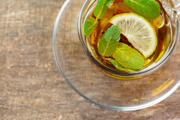 Taza de té negro con hojas de menta en una mesa de madera Foto Premium