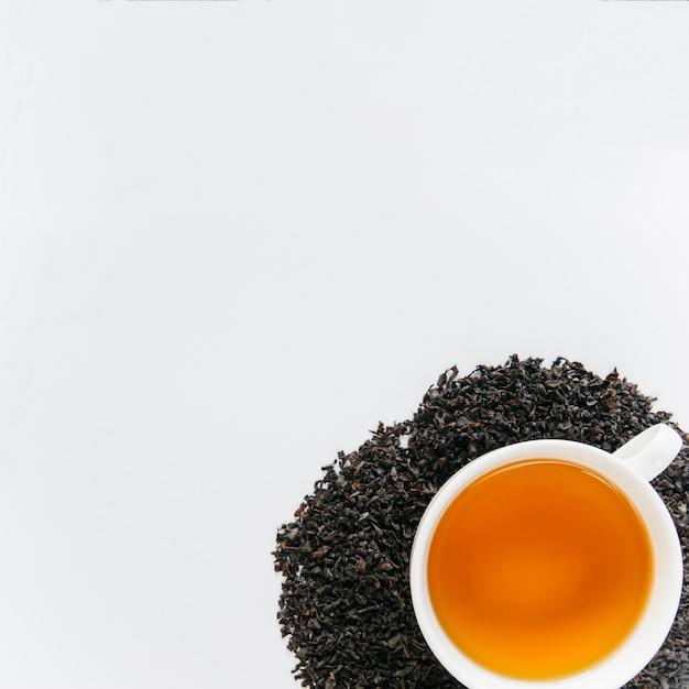 Taza de té negro sobre las hojas secas negras aisladas sobre fondo blanco. Foto gratis