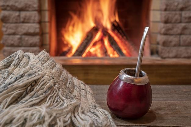Taza tradicional para beber mate y bufanda de lana, cerca de una acogedora chimenea, en casa de campo ,. Foto Premium