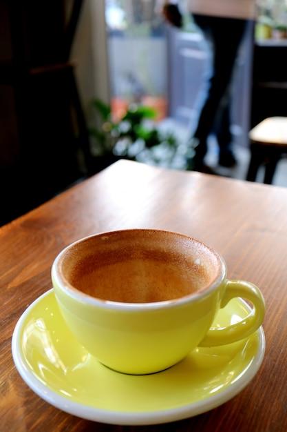 Taza vacía de beber café terminado en la mesa de madera con alguien borroso saliendo de la habitación Foto Premium