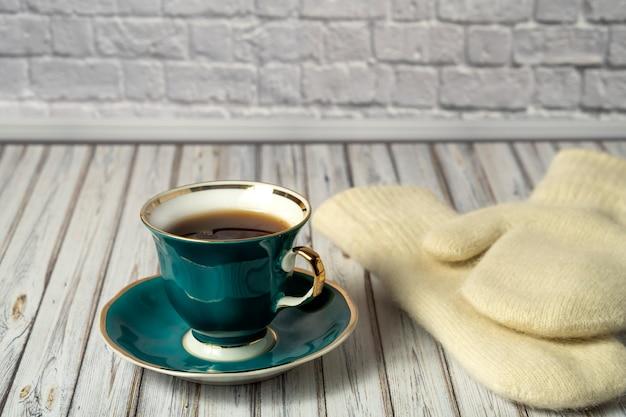Taza verde de té caliente y guantes blancos sobre una mesa de madera Foto Premium