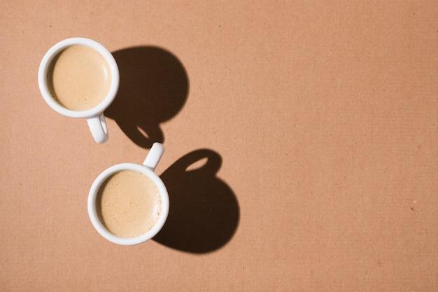 Tazas con café caliente y sombras Foto gratis