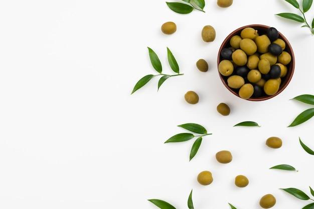 Tazón con aceitunas y hojas y aceitunas extendidas Foto gratis