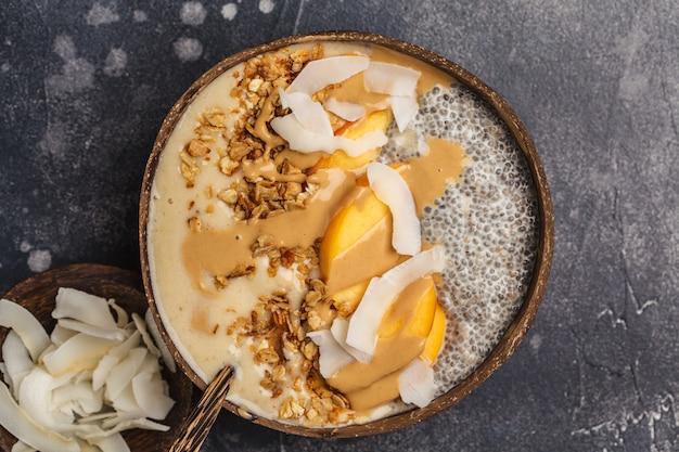Un tazón de batido con pudín de chia, melocotón, coco y granola en un tazón de coco. Foto Premium
