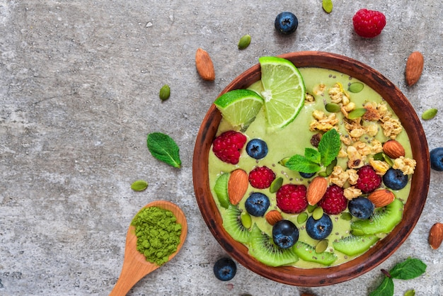 Tazón de batido de té verde matcha con frutas frescas, bayas, nueces, semillas y granola para un desayuno saludable de dieta vegetariana Foto Premium