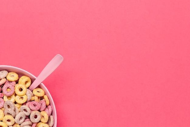 Tazón de bucles de cereales con cuchara en la esquina Foto gratis